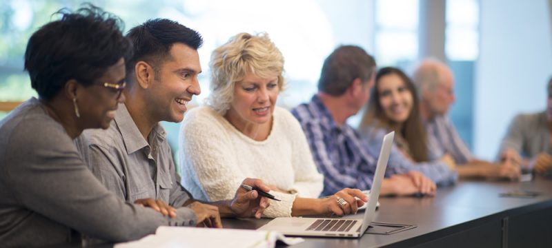 A group of people sitting at a long table collaborating.